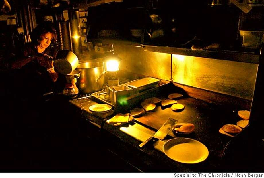 An employee at Nick�s Restaurant in Pacifica makes coffee using the light from a propane lantern on Saturday, Jan. 5, 2008. Like much of the city, Nick�s operated without power Saturday as heavy rains and wind continued to pound the coast. Earlier in day, waves breached a nearby breakwater sending water through the restaurant�s front door. BY NOAH BERGER/SPECIAL TO THE CHRONICLE Photo: Noah Berger
