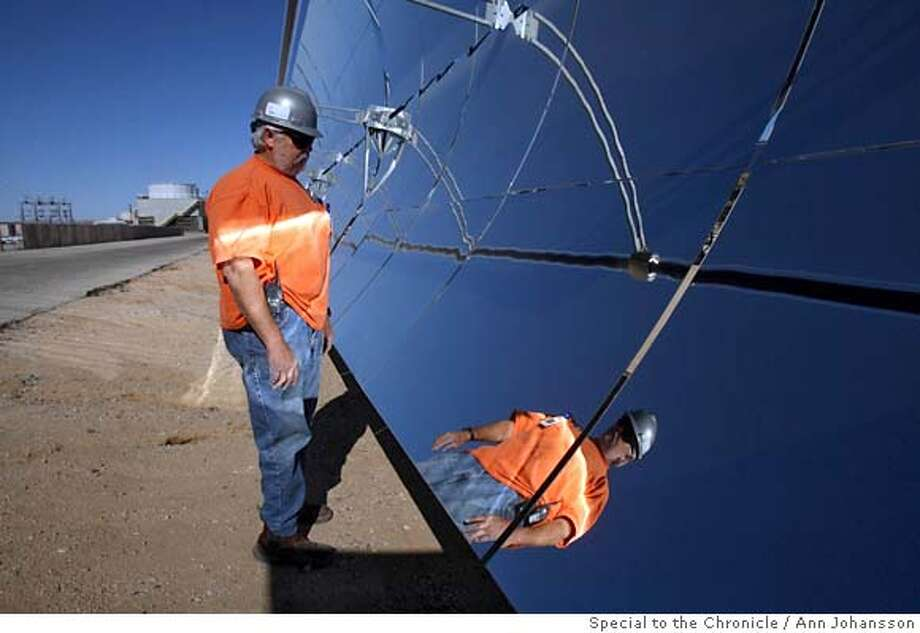 HOLD FOR DAN JUNG...DJ Bob Weggesser shows how curved reflectors concentrates the sunlight, at FPL Energy's Solar Electric Generating System in the Mojave Desert, November 6, 2007. The solar collectors behind them have been turned away from the sun. By Ann Johansson/SPECIAL TO THE CHRONICLE  Ran on: 12-02-2007 Ran on: 12-02-2007 Photo: Ann Johansson