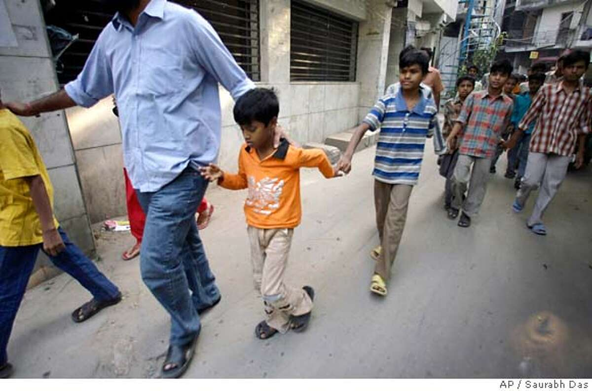 Rescued child laborers are led away from their workplace after child rights activists and policemen raided a small scale garment industry shop in New Delhi, India, Monday Oct. 29, 2007. (AP Photo/Saurabh Das) Ran on: 10-30-2007 Child workers are led away from the sweatshop where they toiled, often without being paid.