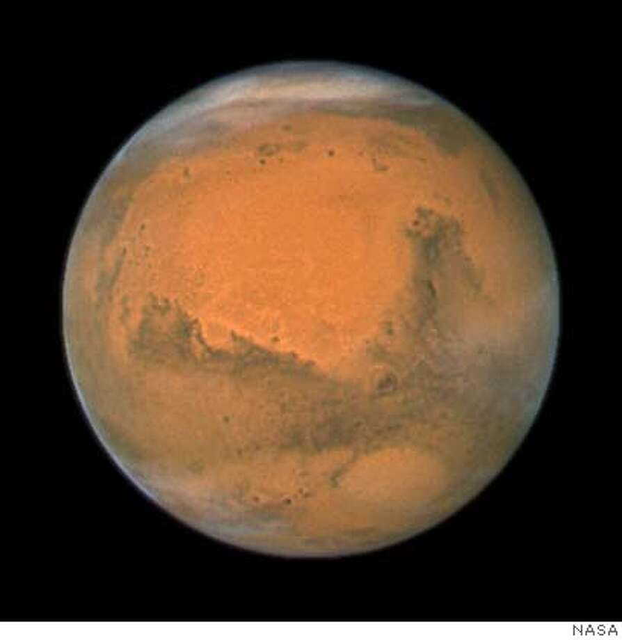 "This image provided by NASA's Hubble Space Telescope shows a close-up of the red planet Mars when it was closest to the Hubble Space Telescope - just 55 million miles (88 million kilometers) away taken with Hubble's Wide Field and Planetary Camera 2. Mars was closest to Earth on Dec. 18, at 11:45 p.m. Universal Time (6:45 p.m. EST). Mars and Earth have a ""close encounter"" about every 26 months. These periodic encounters are due to the differences in the two planets' orbits. The planet appears free of any dust storms during this closest approach, however, there are significant clouds visible in both the northern and southern polar cap regions. (AP Photo/NASA) IMAGE PROVIDED BY NASA Photo: NASA"
