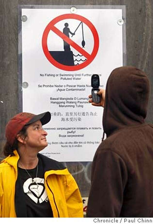 Deckhand April Finn watches Kevin Snow, captain of the Soup Fin II, snap a photo of a sign warning of the hazardous conditions before crab fisherman met in a closed-door session and voted to cancel the upcoming crab fishing season in San Francisco, Calif. on Saturday, Nov. 10, 2007 and wait until the ocean has been cleaned of the oil spilled from the Cosco Busan, which collided with the Bay Bridge Wednesday and leaked 58,000 gallons of oil into the bay.  PAUL CHINN/The Chronicle  **April Finn, Kevin Snow Photo: PAUL CHINN