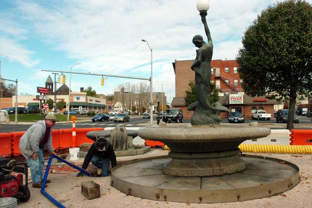 Jack Pereira and Frank DeMelo work to drain a space under the Wheeler Memorial Fountain in Bridgeport, Conn. on Nov. 2nd, 2009. The historic fountain, which was built in 1912, will soon be refurbished after years of neglect and damage from automobile collisions.