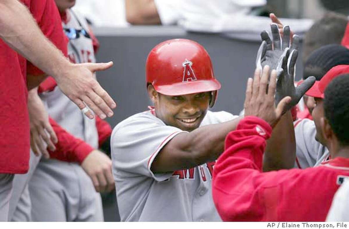 Anaheim Angels' Jose Guillen receives congratulations in the dugout following his fourth-inning home run against the Seattle Mariners, Sunday, July 25, 2004, in Seattle. The Mariners won, 6-2. (AP Photo/Elaine Thompson)