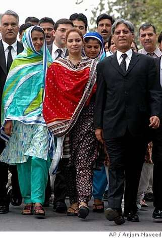 Pakistani rape victim Mukhtar Mai, left, accompanied by her lawyer Aitzaz Ahsan, right, and her supporter Nargis Faiz Malik, center, leaves from Supreme Court after the court decision, Tuesday, June 28, 2005 in Islamabad, Pakistan. Pakistan's Supreme Court overturned the acquittals of 13 suspects in the gang rape of Mai, whose plight drew international attention, and ordered them re-arrested, court officials and a lawyer in the case said. (AP Photo/Anjum Naveed) Mukhtaran Bibi (left), supporter Nargis Faiz Malik (center) and lawyer Aitzaz Ahsan leave the Supreme Court in Islamabad. Photo: ANJUM NAVEED