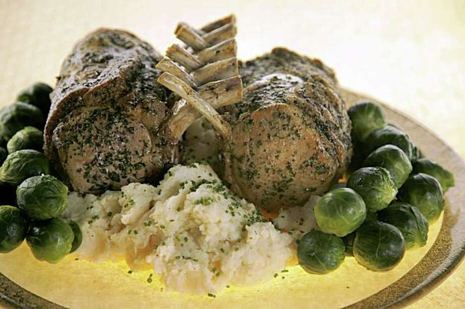 "Herbed Pork ""Guards in Honor"" Roast on mashed potatoes with vegetables garnished around. Photo: Liz Mangelsdorf, SFC"
