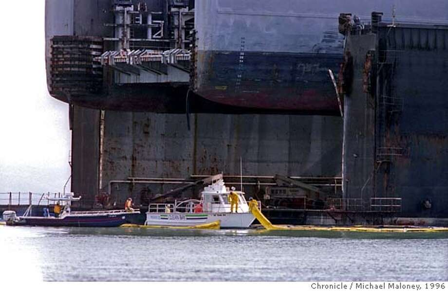 This 10/26/1996 Chronicle file photo shows Clean Bay workers deploying a yellow plastic boom around the ship Cape Mohican to help corral about 8,400 gallons of a heavy fuel oil that spilled into San Francisco Bay. The tanker was in dry dock at Pier 70 for repairs. The Associated Press reported that about 80,000 gallons of bunker fuel leaked from the Cape Mohican, but most of it remained inside the dry dock, said Coast Guard spokeswoman Shelly Freier. About 150 people worked through the night to clean-up the spill.  Photo by Michael Maloney/The Chronicle Photo: Michael Maloney 1996