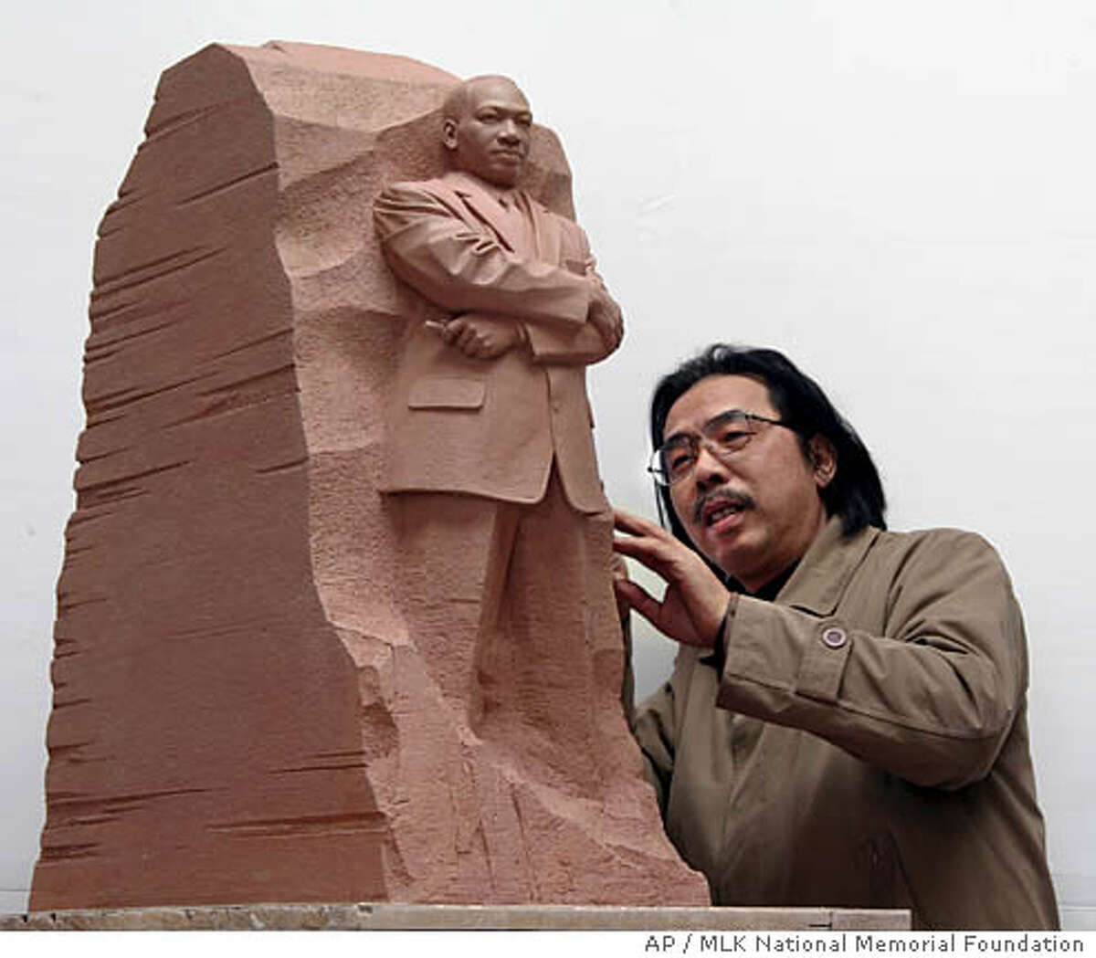 In this undated photograph released by the MLK National Memorial Foundation, sculptor Master Lei Yixin of China looks at a scale model of the