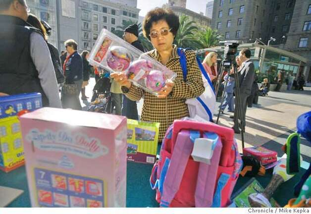 Sheila Kung of San Francisco holds a package of toys display by the Dept. of the Environment that test positive for hight counts of lead. -- At the base of the Christmas tree in Union Square the San Francisco Dept. of the Environment held a press conference about disturbing amounts of lead that some toys have in them. They also offered concerned parents a chance to get there own toys tested for lead content. Mike Kepka / The Chronicle Photo taken on 12/5/07, in San Francisco, CA, USA Photo: Mike Kepka