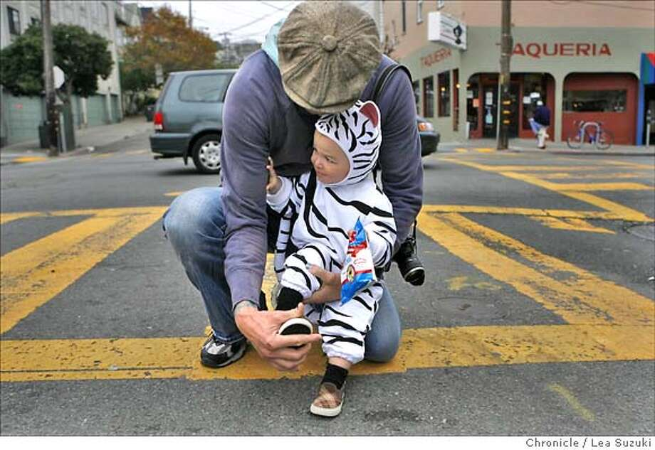 halloween_features_059_LS.jpg  Seni Felic helps his son, Venice, 18 months; put back on a shoe he started to lose while crossing Collingwood Street on their way to the Eureka Valley Recreation Center for a Halloween event. Halloween features from the Castro District. Lea Suzuki / The Chronicle Photo taken on 10/31/07, in San Francisco, CA, USA. Photo: Lea Suzuki