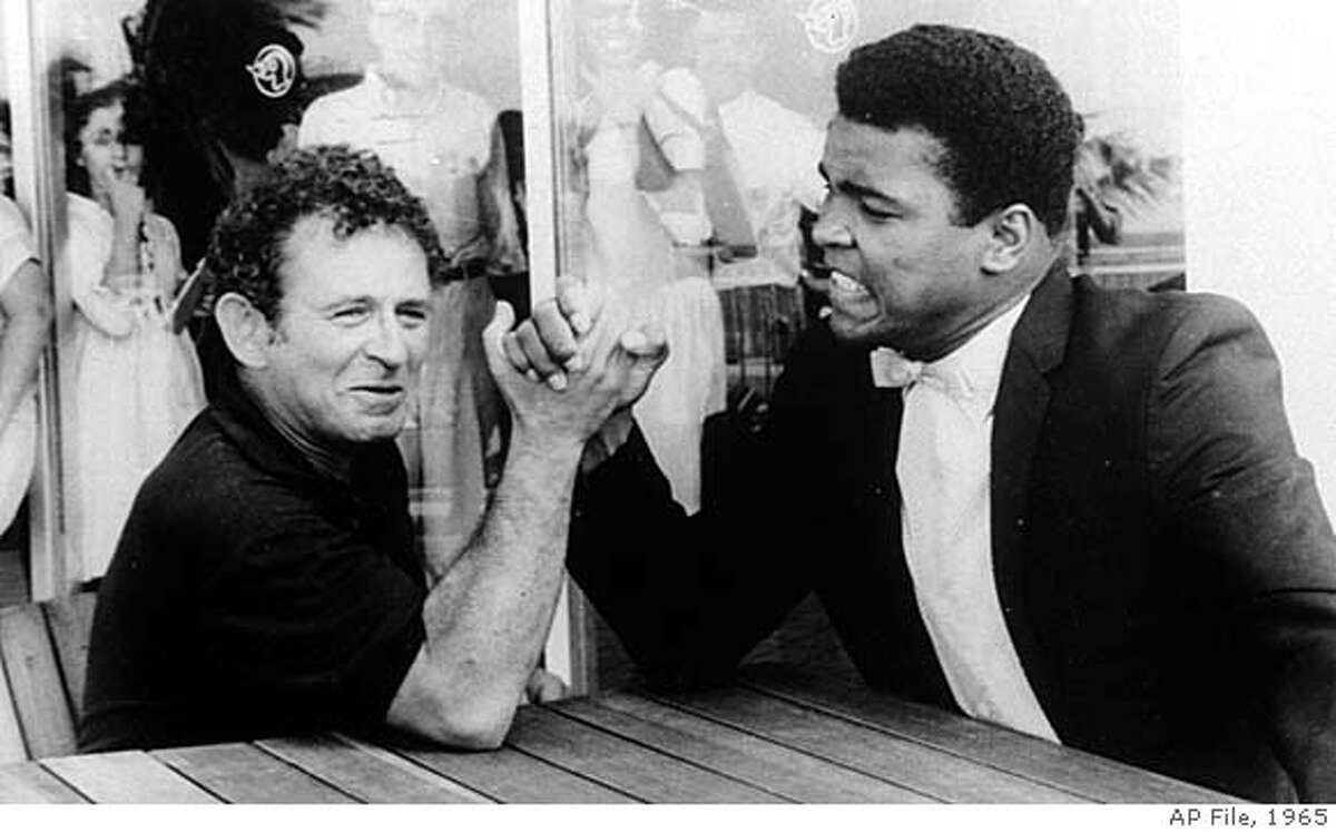 FILE--Novelist Norman Mailer is shown arm wrestling with heavyweight champion Muhammad Ali on the terrace of their San Juan hotel, in this August 1, 1965 file photo. Mailer, the macho prince of American letters who for decades reigned as the country's literary conscience and provocateur, died of renal failure early Saturday, his literary executor said. He was 84. (AP Photo/File)