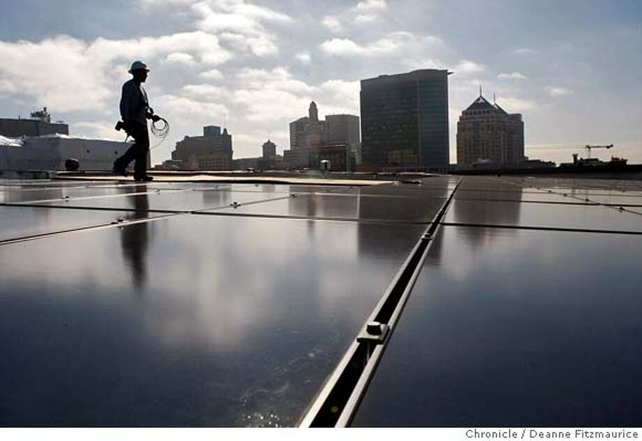 "oaksolar14_186_df.jpg  Luciano Calderon with Century Roof & Solar installs solar panels. Clouds are reflected in the solar panels. the Oakland Federal Building is at far right. The Solar panels are installed on the roof of an Alameda County social services building at Thomas L. Berkley Square (cq) in Oakland which is part of a project that urban developers hope will be a major step in the ""greening"" trend in the Bay area. Deanne Fitzmaurice / The Chronicle Mandatory credit for photographer and San Francisco Chronicle. No Sales/Magazines out. Photo: Deanne Fitzmaurice"