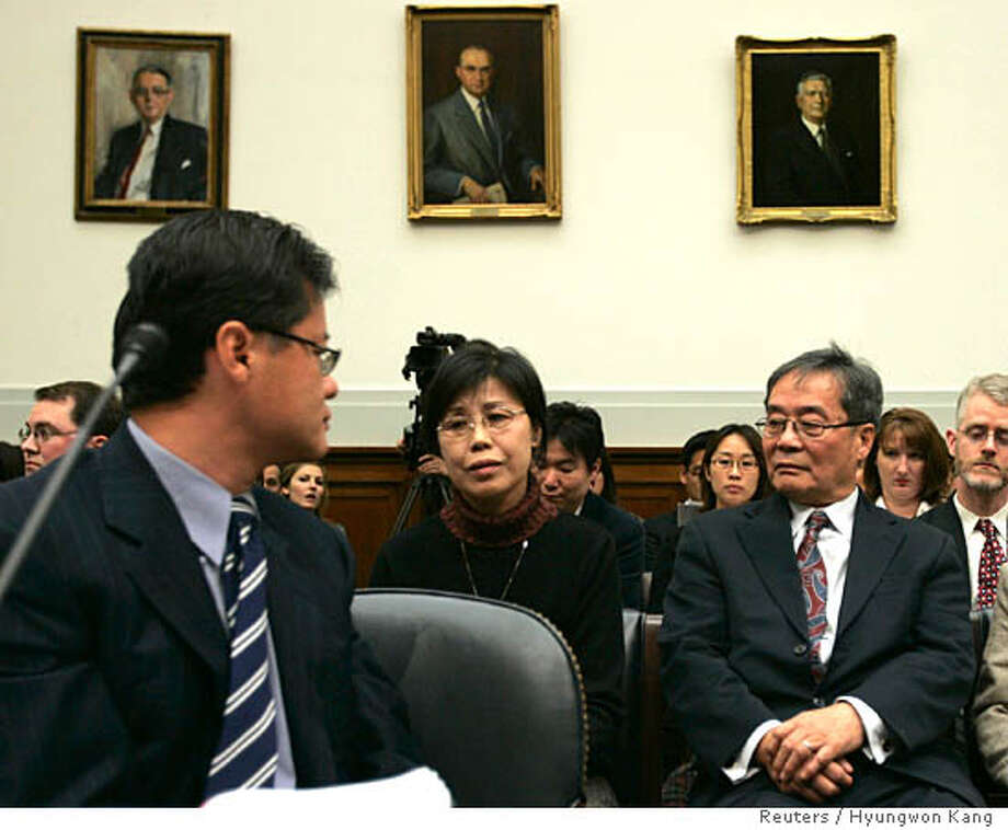 "CEO of Yahoo! Inc. Jerry Yang looks at Gao Qin Sheng (C), mother of Shi Tao, a Chinese reporter who was sentenced last April to 10 years in prison for leaking state secrets abroad, and Chinese dissident Harry Wu (R), as he testifies before a U.S. House Foreign Affairs Committee hearing on Capitol Hill in Washington November 6, 2007. The committee is hearing on ""Yahoo! Inc.'s Provision of False Information to Congress"" regarding the American company's role in landing Chinese journalist Shi Tao behind bars in China. Yang offered his apology to the families affected by Yahoo's cooperation with the Chinese government. REUTERS/Hyungwon Kang (UNITED STATES)  Ran on: 11-14-2007  Yahoo CEO Jerry Yang (left) testifies on Capitol Hill. Behind him is Gao Qin Sheng (center), mother of jailed reporter Shi Tao. Photo: HYUNGWON KANG"