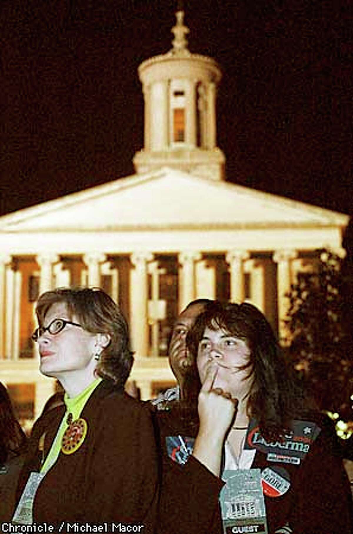 GORENIGHT1-C-07NOV00-MN-MAC Al Gore Election night headquarters in Nashville Tennessee. the Tennesse Stae Capitol building in the background of Gore supporters Barbara Quinn, Terry Rainey and Samantha Rainey. The three watch election returns on big screen TV's at the War Memorial Building. by Michael Macor/The Chronicle