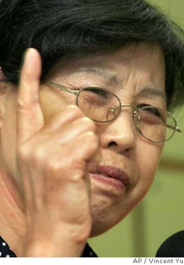 Gao Qinsheng, mother of jailed Chinese journalist Shi Tao, reacts during a news conference in Hong Kong Sunday, June 10, 2007. Shi Tao, a jailed Chinese reporter accused of leaking state secrets has joined a U.S. lawsuit claiming Yahoo Inc. helped the Chinese government convict dissidents, his mother said Sunday. Shi Tao, who was sentenced in 2005 to 10 years in prison, is seeking compensation from the Sunnyvale, California-based Internet company because Yahoo Hong Kong and Yahoo China were accused of providing information to the Chinese authorities that led to his arrest. (AP Photo/Vincent Yu)  Ran on: 06-12-2007  Gao Qingsheng, mother of jailed journalist Shi Tao, who has been accused of leaking state secrets in China, has joined a lawsuit against Yahoo Inc. Photo: Vincent Yu