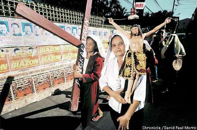 Women carried crosses past old election posters after attending Mass. Religion plays an important part in the presidential crisis. Photo by David Paul Morris special to the Chronicle