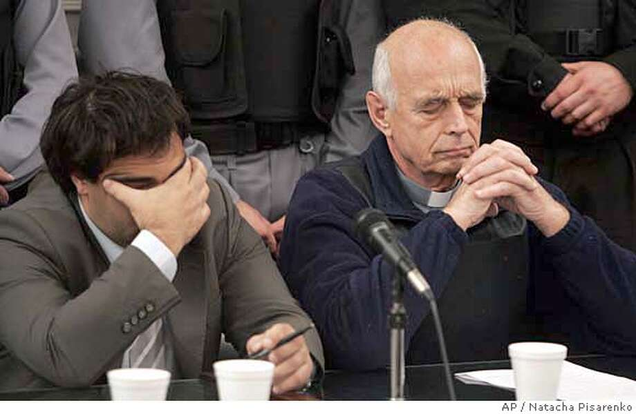 """Former police chaplain Christian Von Wernich, right, accompanied by his lawyer Marcelo Pena, reacts after the verdict was pronounced in a trial in La Plata, Argentina, Tuesday, Oct. 9, 2007. Von Wernich is the first Roman Catholic priest to be charged for crimes committed under Argentina's dictatorship, was convicted and sentenced to life in prison in a trial that focused attention on church's role in the military's """"dirty war"""" on opponents. (AP Photo/Natacha Pisarenko) EFE OUT Photo: Natacha Pisarenko"""