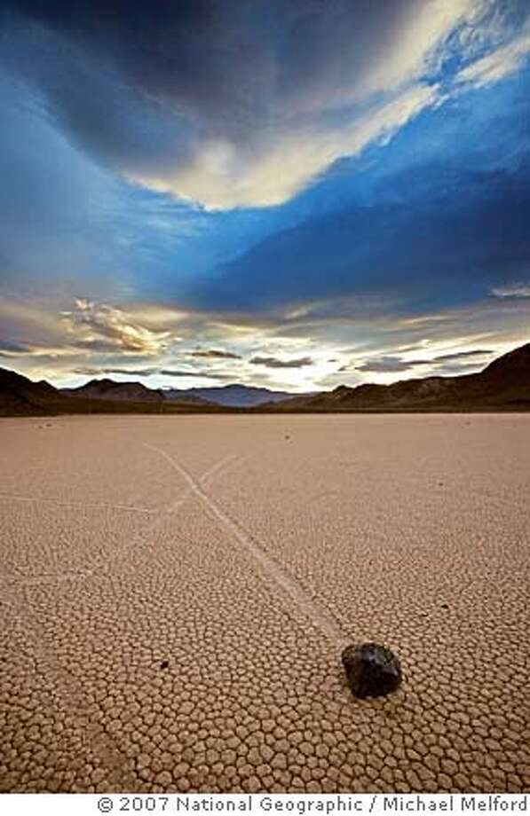 TRAVEL DEATH VALLEY -- When the playa called the Racetrack gets wet, rocks of up to 700 pounds are believed to catch a wind and skim across like pucks on ice. No one�s seen it happen, but tracks tell the tale. Credit: Michael Melford / National Geographic FOR YOUR ONE-TIME EXCLUSIVE USE ONLY AS A TIE-IN WITH THE 2007 ISSUE OF NATIONAL GEOGRAPHIC MAGAZINE. NO SALES, NO TRANSFERS. NO USE EXCEPT TRAVEL SECTION 11/04 Photo: Michael Melford