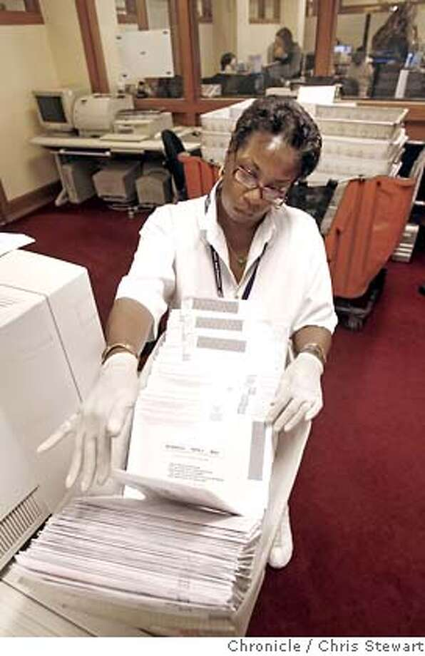 San Francisco election clerk Donna Hopkins (cq) examines absentee ballots for missing signatures in the Department of Election office at City Hall. Photographed November 6, 2007.  Chris Stewart / The Chronicle Photo taken on 11/6/07, in San Francisco, CA, USA Donna Hopkins, absentee ballots, election, San Francisco Photo: Chris Stewart