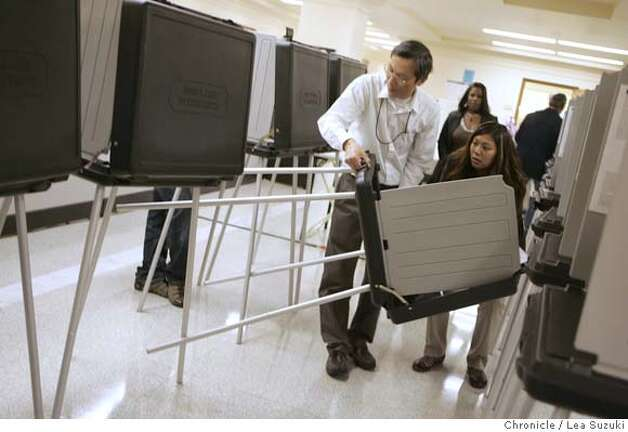 election06_012_ls.jpg  From left: Steven Ku, AV counter and Rachel Gosiengfiao, campaign services manager, upright a polling booth that fell over at City Hall. Absentee voters at City Hall on Monday.  Lea Suzuki / The Chronicle Photo taken on 11/5/07 in San Francisco, CA, USA. Photo: Lea Suzuki