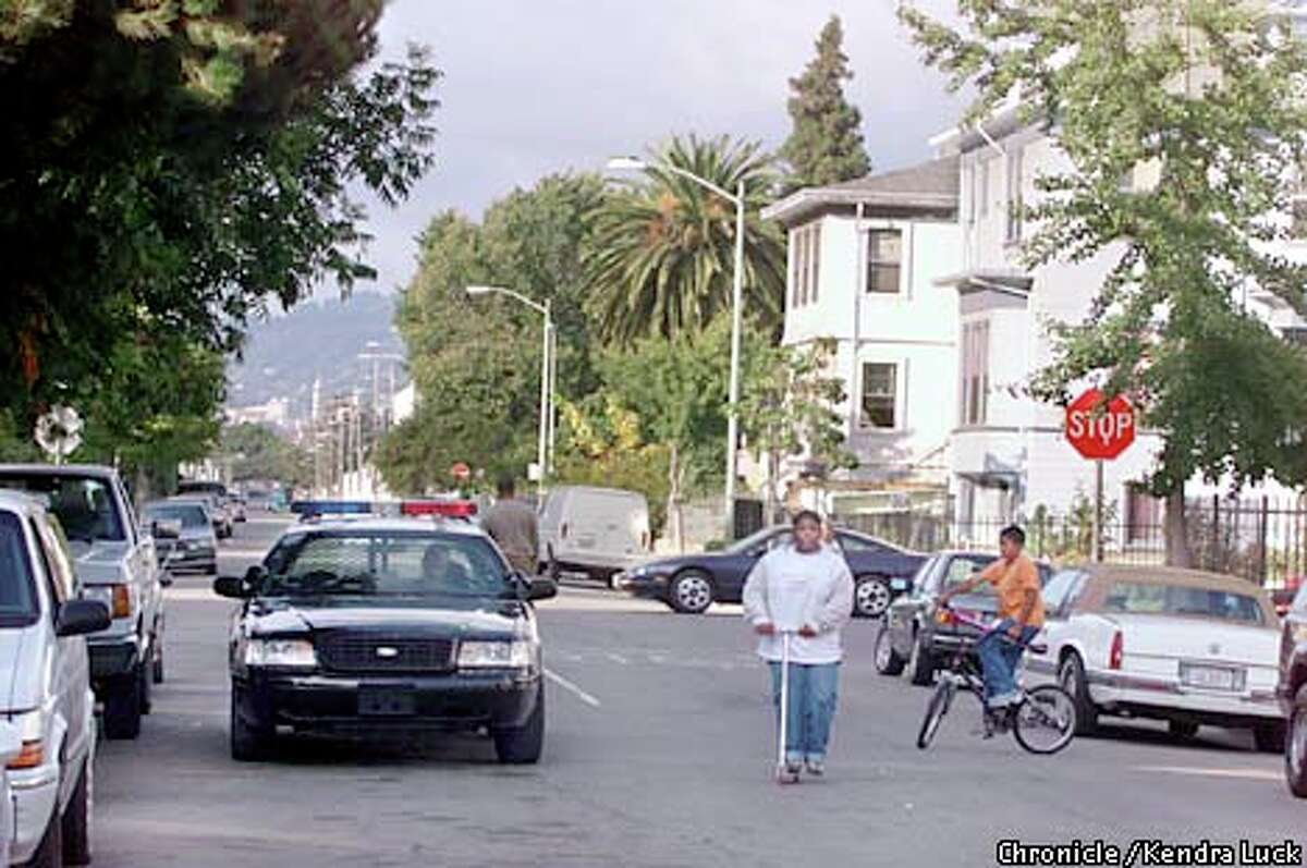 A police car drives down Myrtle Street in West Oakland. Chronicle photo by Kendra Luck