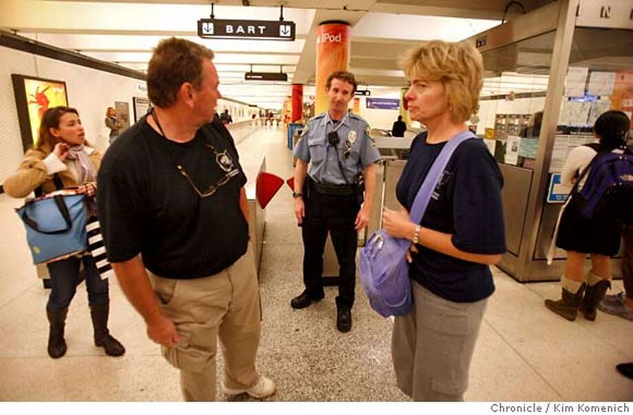 BART Community Services Officer Martin Croskery (Center) breaks the bad news to would-be passengers David Barnett (to the left of Croskery) and Jana Gantley (to the right of Croskery), both visiting from Kentucky, after BART is shut down during Tuesday's commute as a body is removed from the tracks mid-platform at the Powell Street Station.  Photo by Kim Komenich/The Chronicle  **Darvid Barnett, Jana Gantley, Martin Croskery Photo: Kim Komenich