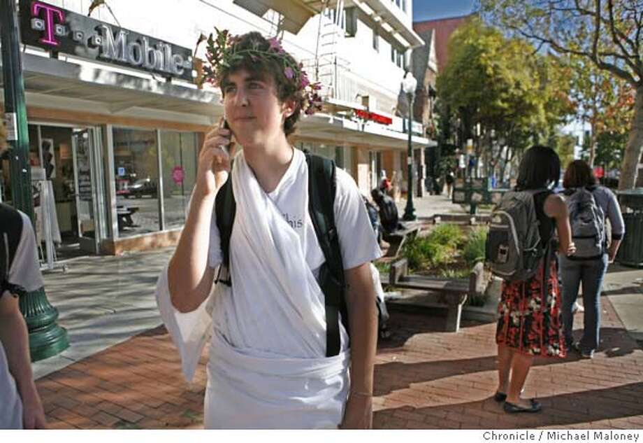 Dan Lewis, a 16 year old junior at Berkeley High School uses his cell phone to call a friend while he waits for a bus outside a T-Mobile store on Shattuck Ave. in Berkeley. Tuesday is Toga Day at Berkeley High which explains the toga and laurel wreath. Lewis said he has no problems using his cell phone in Berkeley except for inside a few buildings on campus.  Cell phone companies would like to erect more cell towers in the the city of Berkeley. Berkeley declared a moratorium on cell phone towers six years ago, citing concerns that the towers transmit hazardous waves. However Verizon is saying a federal law bans cities from blocking transmissions. Photo taken on 10/23/07 in Berkeley, CA.  Photo by Michael Maloney / San Francisco Chronicle  ***Dan Lewis (cell : 510-590-8409) MANDATORY CREDIT FOR PHOTOG AND SF CHRONICLE/NO SALES-MAGS OUT Photo: Michael Maloney