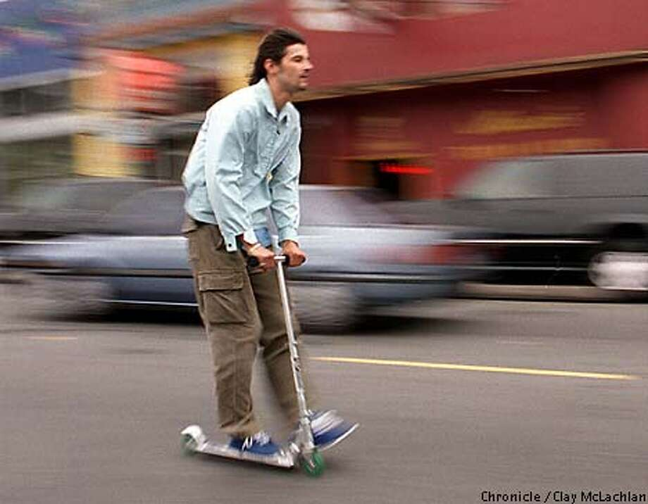 Alex Cerny, a bartender who commutes from Pacific Heights to South of Market on his scooter, glided down Haight Street. Chronicle photo by Clay McLachlan