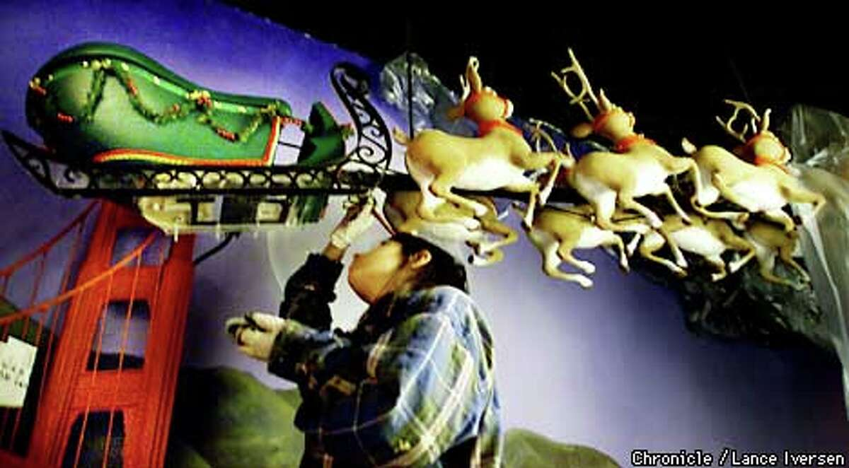 Jennifer Varbalow, an employee of New York's Spaeth Design, puts the finishing touches on Santa's sleigh for Macy's holiday window display. The display consists of six windows in two stores. Chronicle photo by Lance Iversen