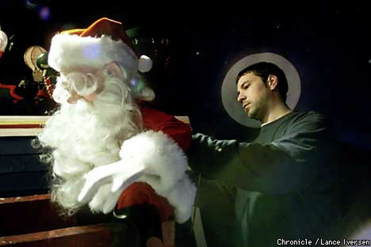 """Animator Eric Novak prepares Santa for the Disney-inspired window display at Macy'sn in downtown San Francisco. The display is based on clement Clarke Moore's 1823 poem, """"A visit from St. Nicholas."""" Chronicle photo by Lance Iversen"""