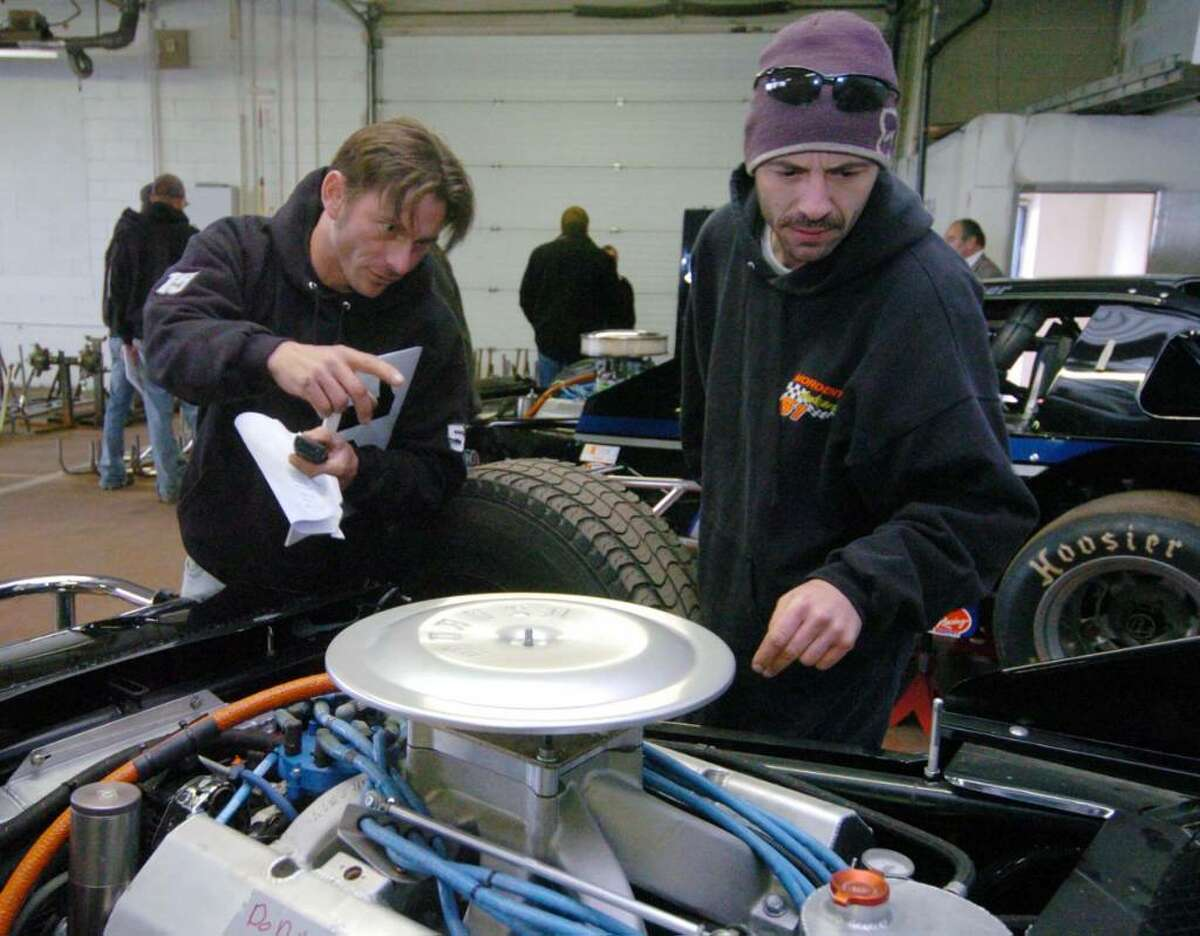 From left, Gary Knight, of Charlestown, NH and Warren Mordenti, of Newport, NH, look over cars prior to an auction of seized property of James Galante's at Metro Auto Body & Towing in Harford, CT, Friday, Nov. 6, 2009. The property consisted of racing cars and parts.
