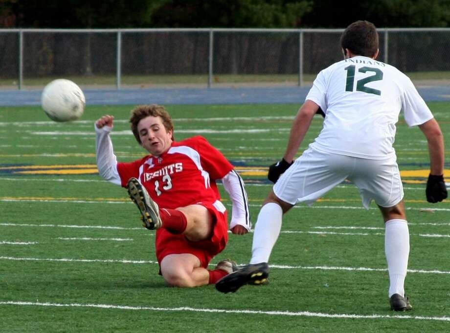 Fairfield Prep's #13 Matthew Leonard slides and kicks the ball away from Guilford's #12 Ben Colter, during SCC soccer action in East Haven, Conn. on Friday Nov. 06, 2009. Photo: Christian Abraham / Connecticut Post
