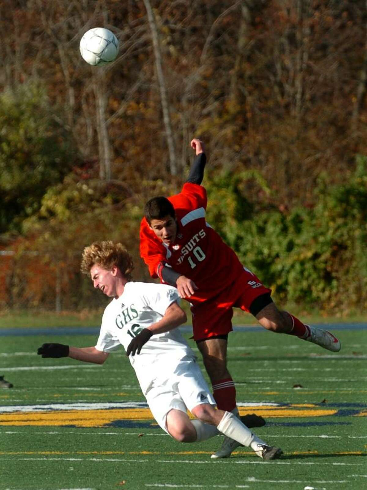 Fairfield Prep's #10 Sofian Ahtchi, right, and Guilford's #16 Michael Jacobsen fall after colliding, during SCC soccer action in East Haven, Conn. on Friday Nov. 06, 2009.