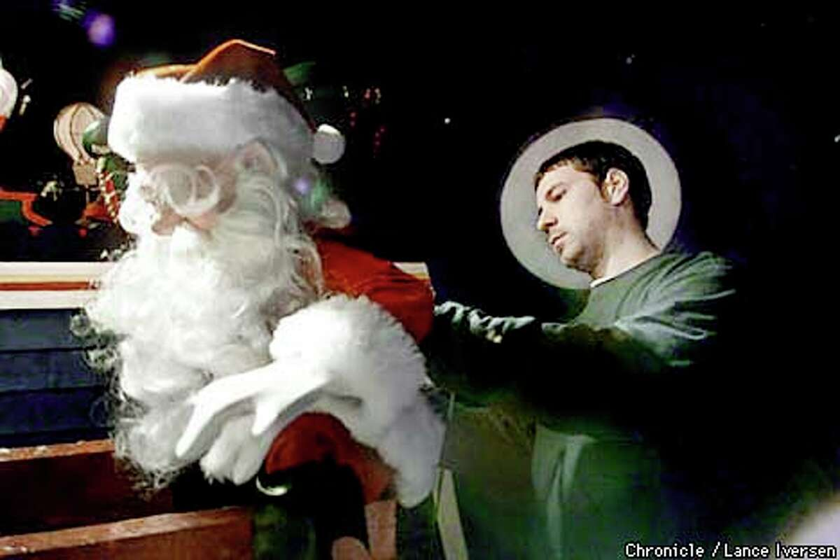 Eric Novak makes adjustments to a mechanical Santa for Macy's window. Chronicle photo by Lance Iversen