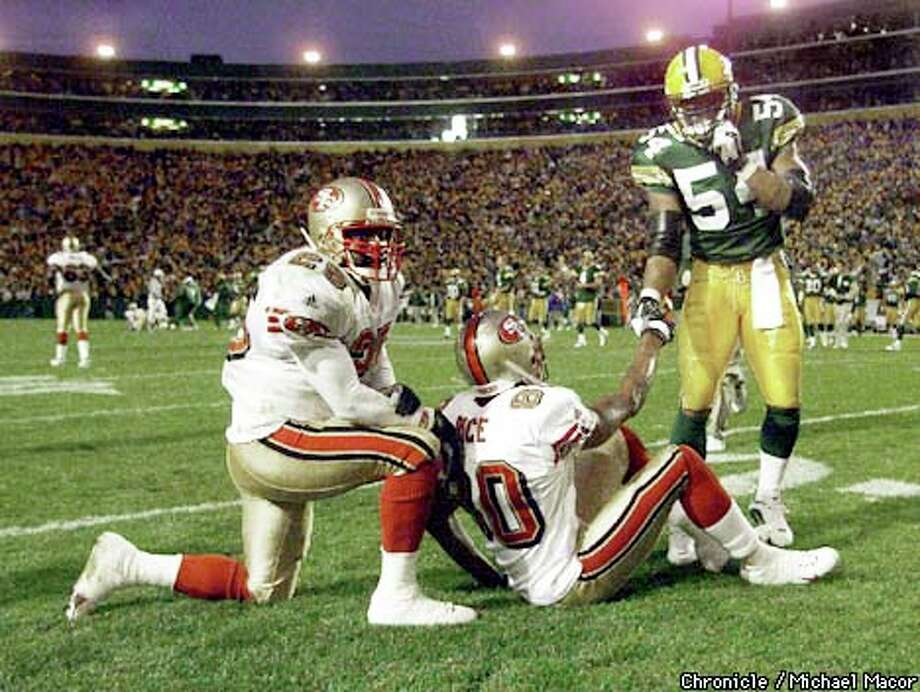 The 49ers' Jerry Rice (sitting) got a hand from Green Bay's Nate Wayne after a completed pass to Charlie Garner (left) came up short to end the game. Chronicle photo by Michael Macor / CHRONICLE