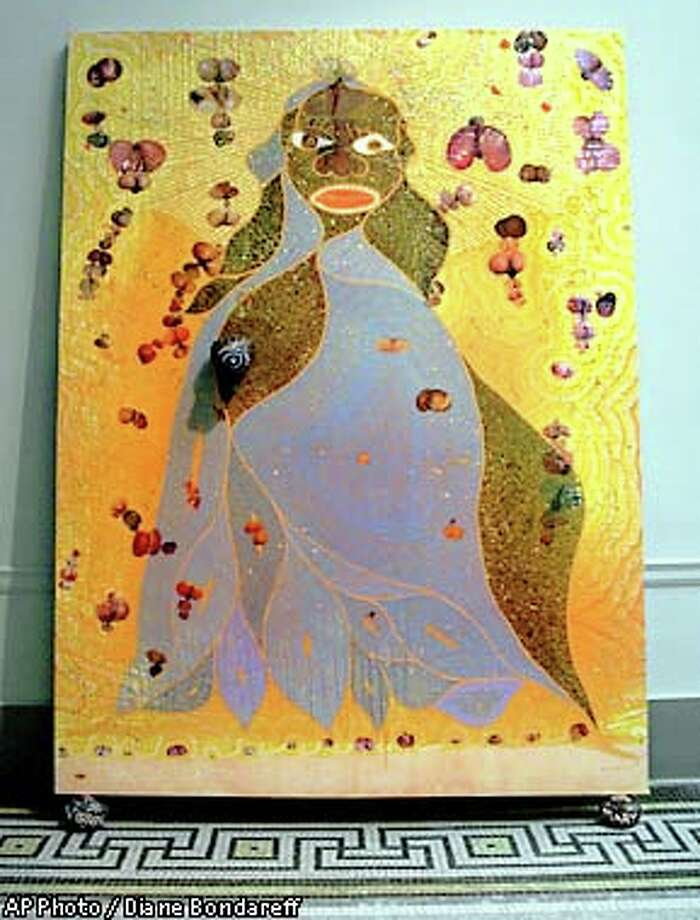 """Chris Ofili's """"The Holy Virgin Mary,"""" a controversial painting of the Virgin Mary embellished with a clump of elephant dung and two dozen cutouts of buttocks from porn magazines, was displayed at the Brooklyn Museum of Art in 1999. New York City Mayor Rudy Giuliani tried to withdraw funding from the museum, but did not win in court. However, the artwork was vandalized by white paint and manure.Source:Religion News Service"""