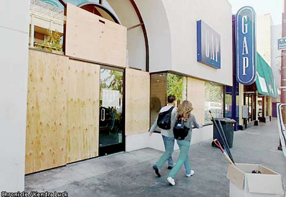 The display windows of the Gap, one of the stores looted in the Saturday night disturbance, were boarded over after the cleanup yesterday. Chronicle photo by Kendra Luck