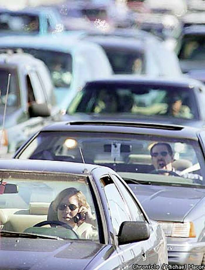 A driver waiting at the Bay Bridge toll plaza passed the time on a cell phone, one of a growing number of distractions for Bay Area commuters. Chronicle photo by Michael Macor