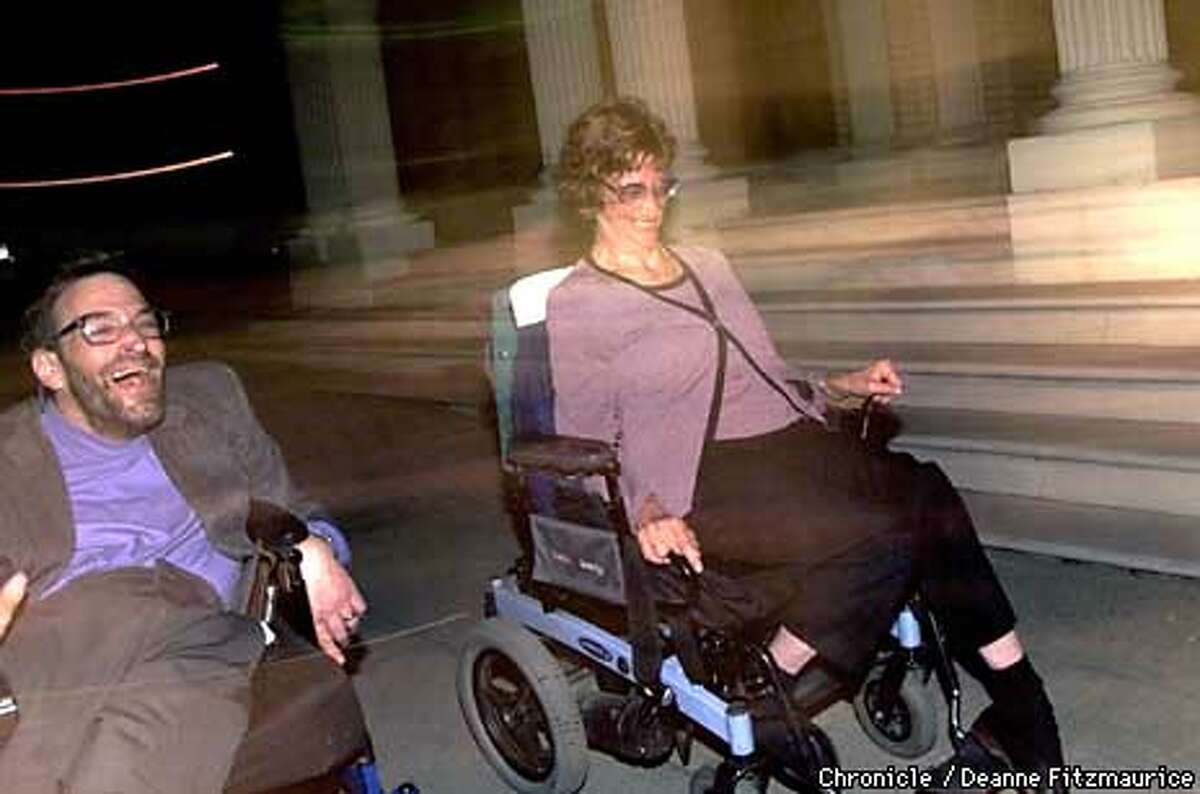 Neil and Denise Jacobson, who both have cerebral palsy, raced their wheelchairs to their van after attending the evening service at their synagogue, Temple Sinai, in Oakland. Chronicle photo by Deanne Fitzmaurice