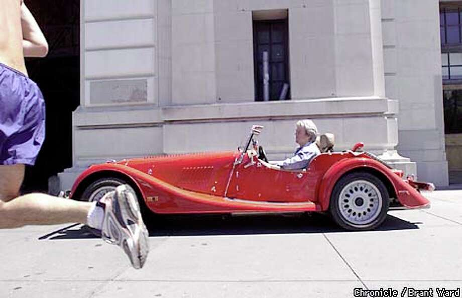Fink cruises the Embarcadero in one of his Morgans as a jogger flashes past. Chronicle Photo by Brant Ward