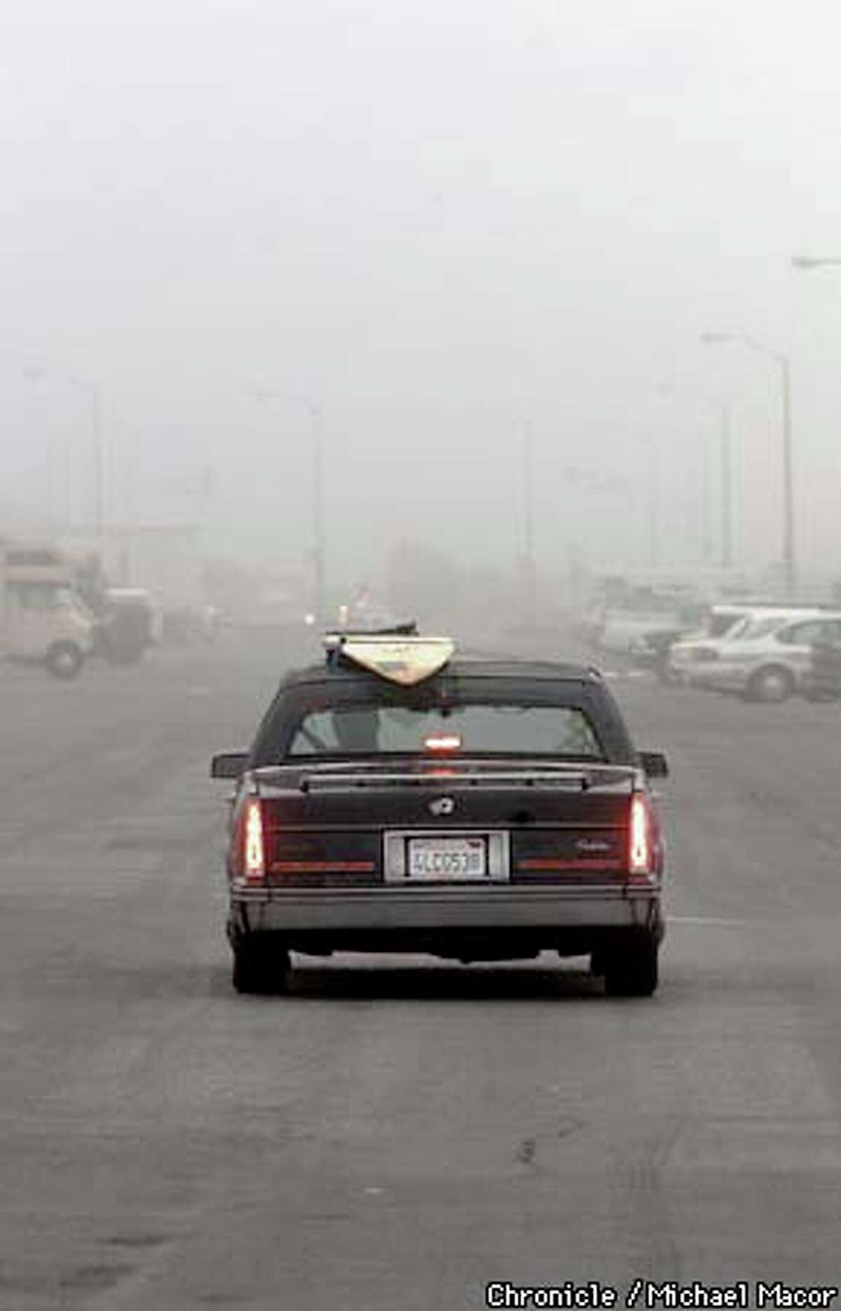 About 8 a.m., Orsi guides his 1987 Cadillac -- with surfboard strapped atop it -- out of the Ocean Beach parking lot as he heads off to work. Chronicle photo by Michael Macor