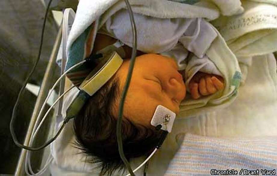 Four-hour-old Olman Acosta slept during a hearing test. The painless procedure measures brain activity to tell if infants are hearing. Chronicle photo by Brant Ward