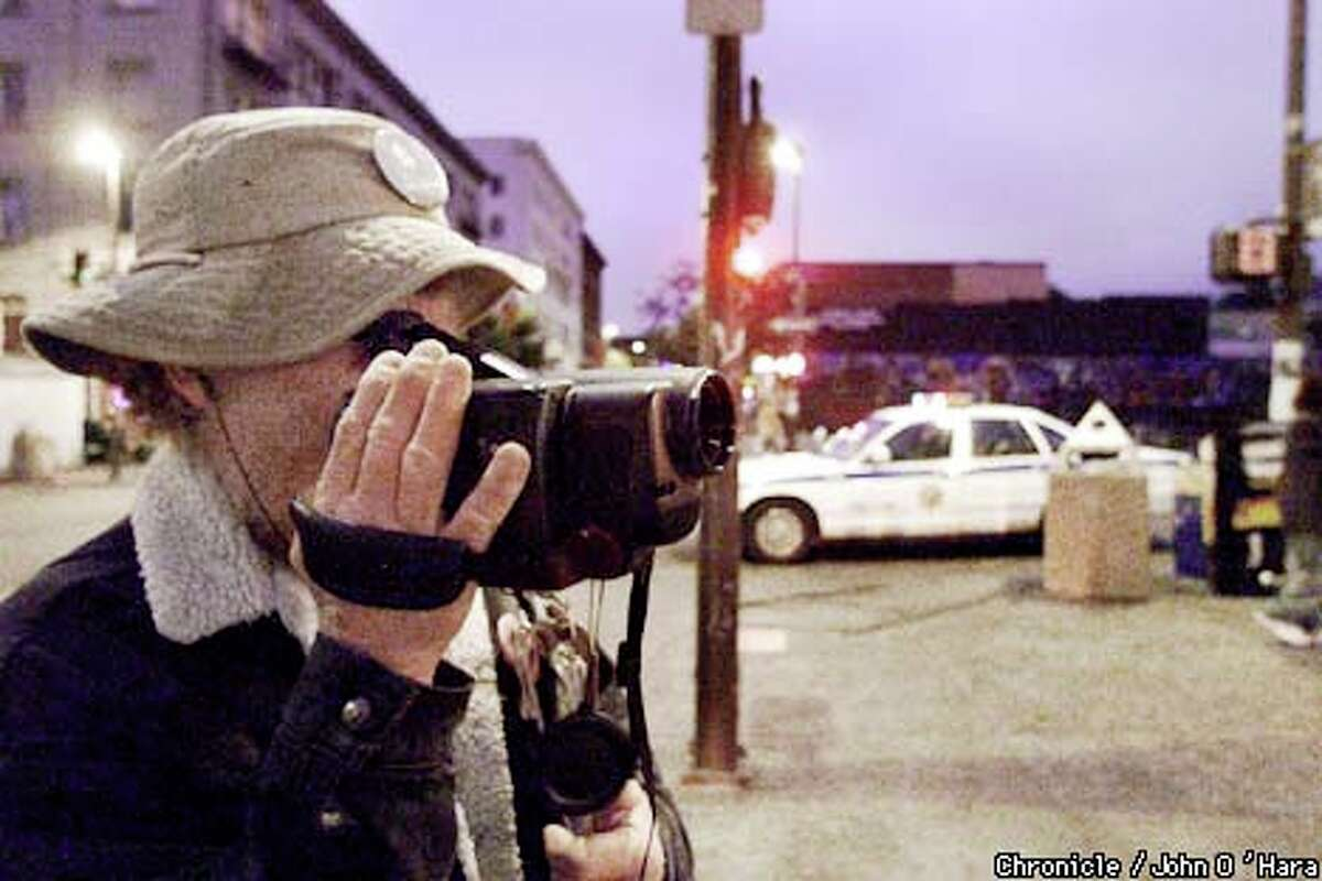 Copwatch member Russell Bates (right) stands outside Amoeba Records on Telegraph Avenue in Berkeley, videotaping the Berkeley police in action. Chronicle photo by John O'Hara