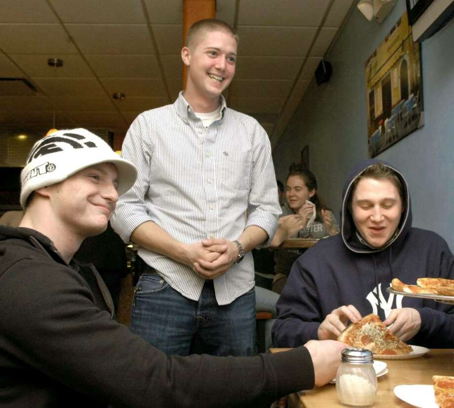 Derek B. Roy, 21, center talks to fellow WestConn students at Soho Pizza about his initiative called Communiversity Thursday, November 5, 2009. Left to right are, Chris Munson, 21 and Brien McCarthy. Photo: Carol Kaliff / The News-Times