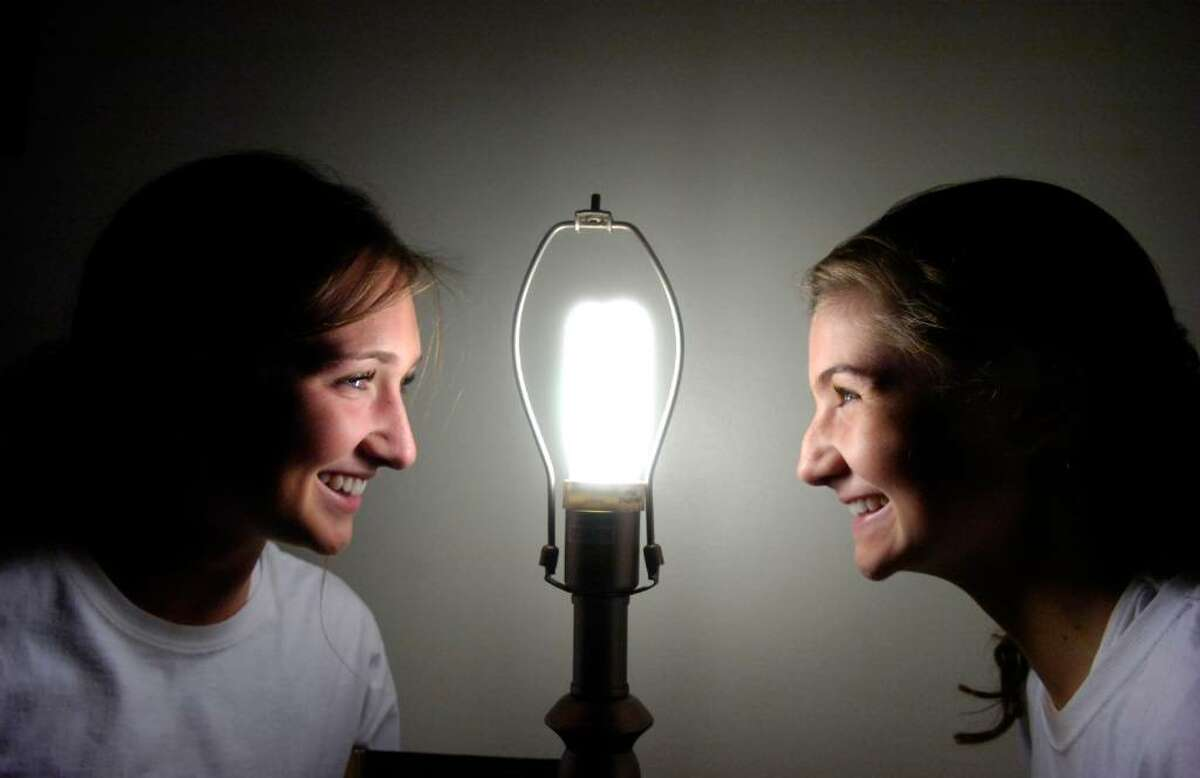 Sisters Lucy, 17, left, and Georgia Williams, 15, are the brains behind Relight Connecticut, a program aimed at giving energy saving lightbulbs to lower income residents helping them conserve energy. They are lit by one of their bulbs in the Armstrong Court home of Helen Brown Thursday evening, Nov. 5, 2009.