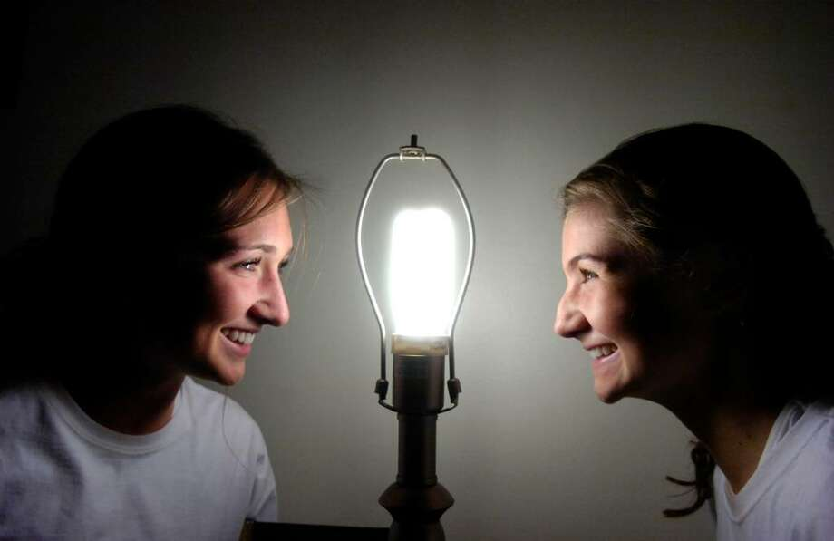 Sisters Lucy, 17, left, and Georgia Williams, 15, are the brains behind Relight Connecticut, a program aimed at giving energy saving lightbulbs to lower income residents helping them conserve energy. They are lit by one of their bulbs in the Armstrong Court home of Helen Brown Thursday evening, Nov. 5, 2009. Photo: Keelin Daly / Greenwich Time