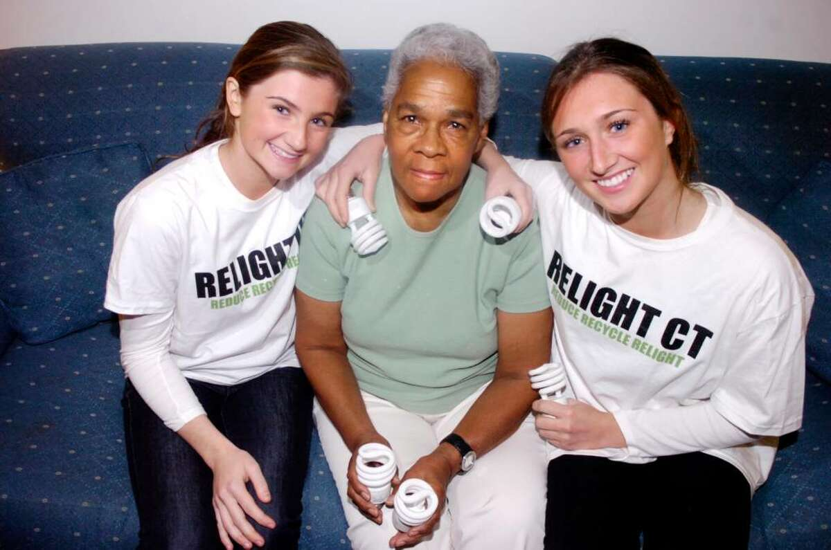 Sisters Georgia, left, 15, and Lucy Williams, 17, are the brains behind Relight Connecticut, a program aimed at giving energy saving lightbulbs to lower income residents helping them conserve energy. They are photgraphed with Helen Brown in her Armstrong Court home Thursday evening, Nov. 5, 2009.