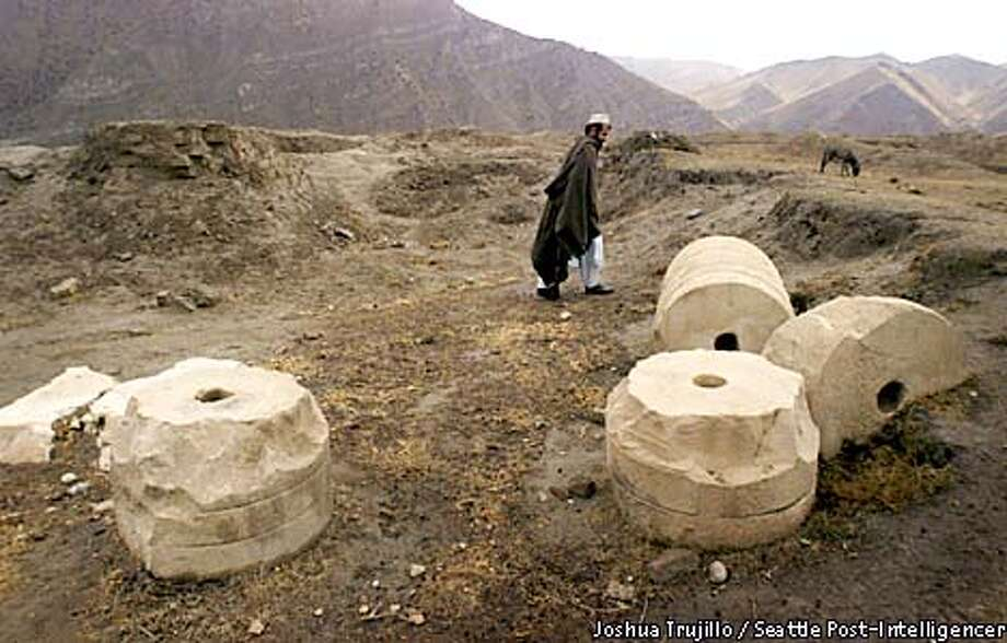 Mahbuhbullah, a dealer of historic artifacts, walks near tumbled stone columns at Ai Khanum, a palace of Alexander the Great, in northern Afghanistan near the Tajikistan border. Mahbuhbullah has a stash of artifacts that he buried in territory now controlled by the Taliban. He estimates the value at about $1 million. The Northern Alliance recently used some of the stone columns for target practice and destroyed intricate carvings over 2,300 years old.  Photo by Joshua Trujillo/Seattle Post-Intelligencer  Hearst Newspapers