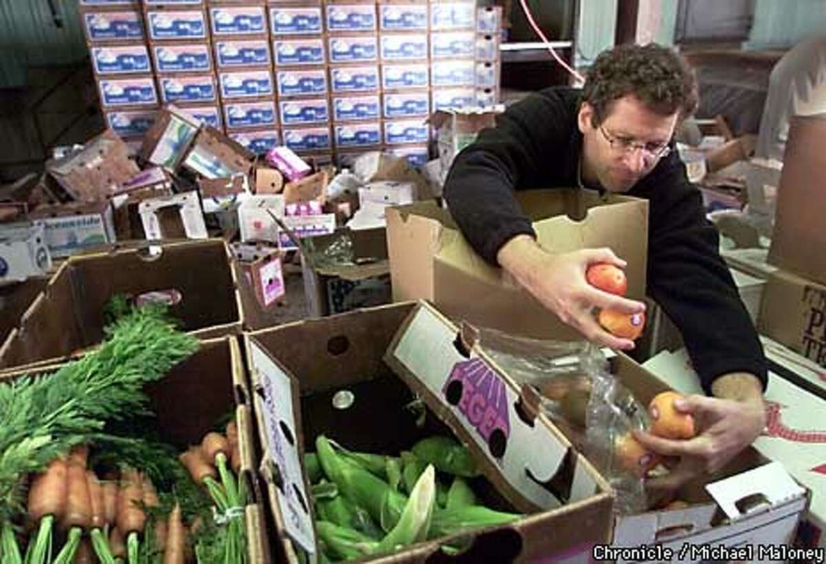 Larry Bearg of Planet Organics packed fruits and vegetables that are sometimes bartered through an online service. Chronicle photo by Michael Maloney