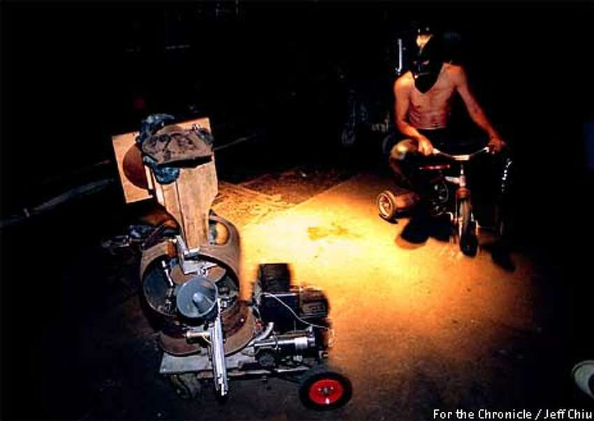 Randy Fortes, a.k.a. ``Gimpy,'' rides a tricycle around the robot Godfella during a performance of the Omnicircus' ``Scabaret,'' which was publicized on the Squidlist. For the Chronicle by Jeff Chiu