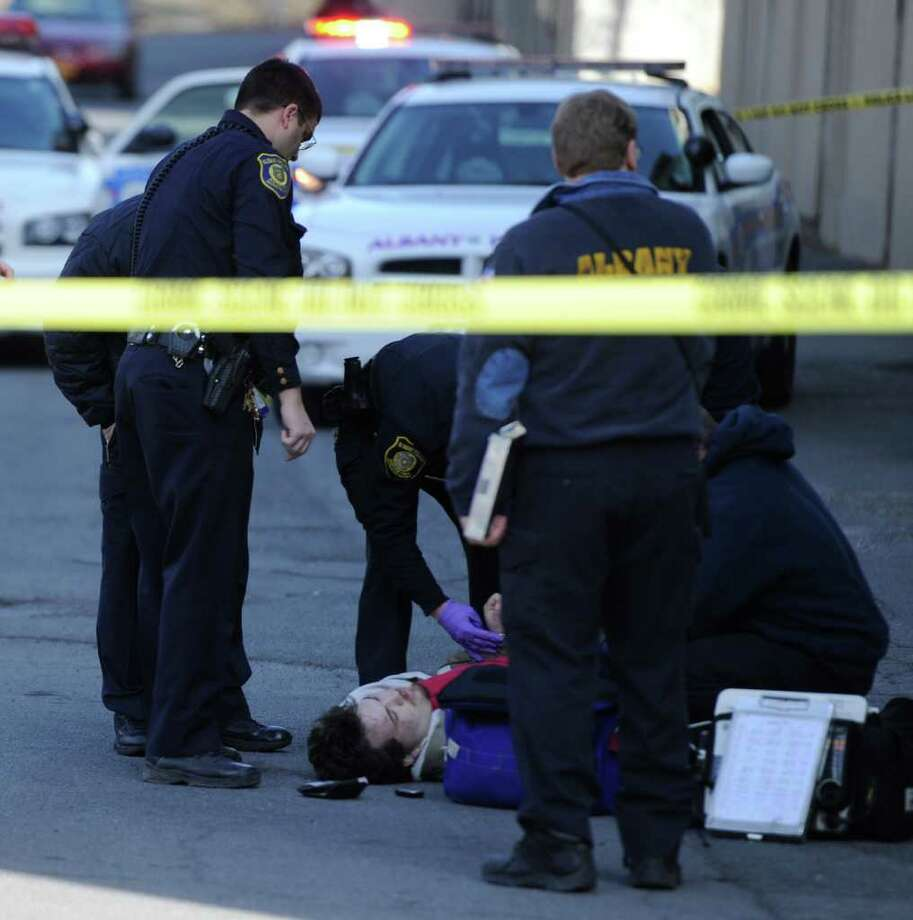 The victim of a gunshot wound is attended to by Albany Fire Department Paramedics behind the an apartment complex at 6 Brevator Street in Albany, N.Y. Feb. 10, 2012.   (Skip Dickstein / Times Union) Photo: SKIP DICKSTEIN / 2011